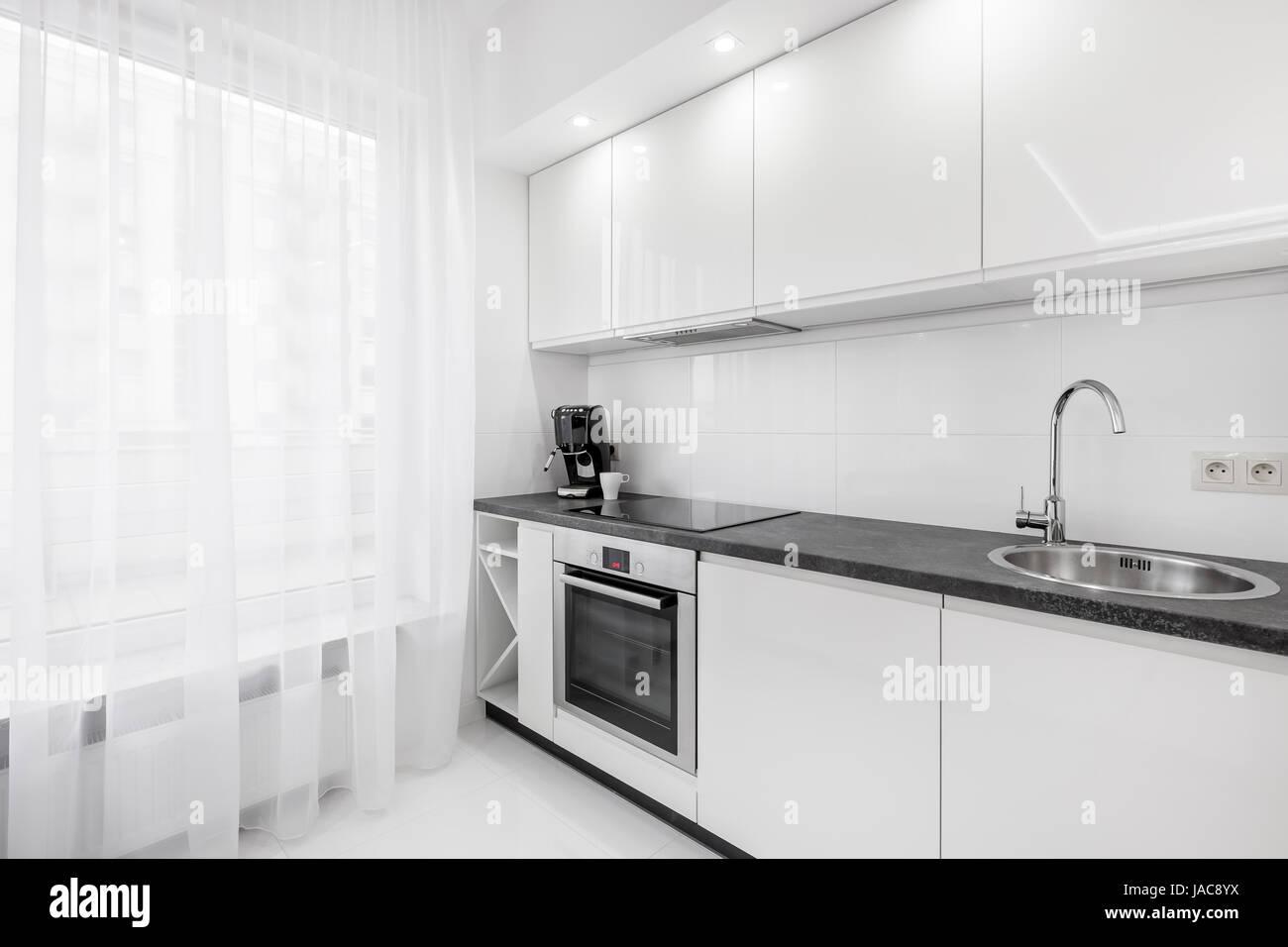 Moderne, weisse Küche mit schwarzen Arbeitsplatte, Spüle, Schränke ...