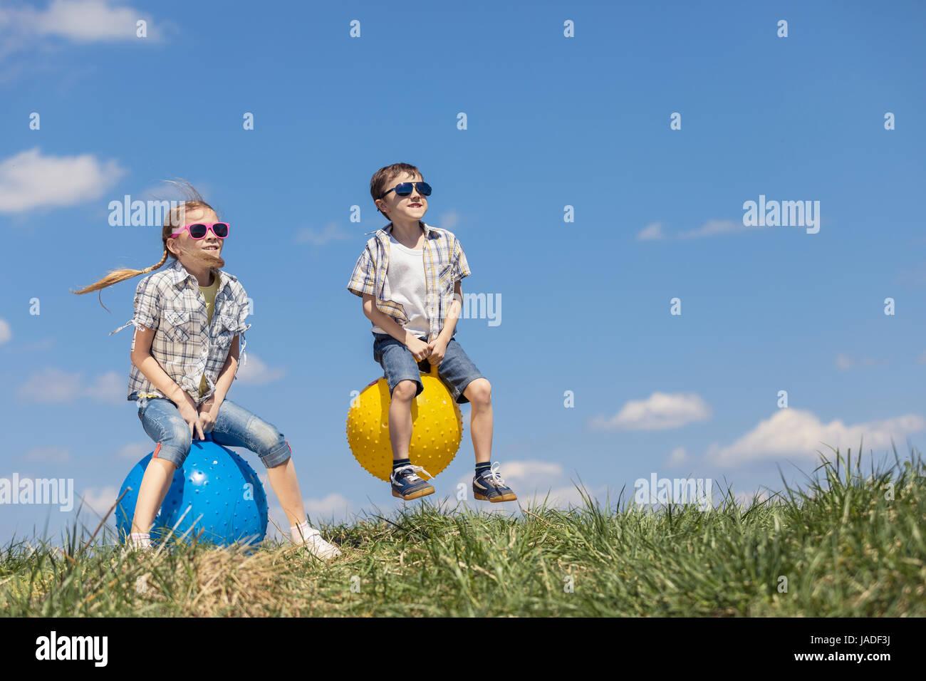 Bruder und Schwester spielen auf dem Feld in der Tageszeit. Kinder haben Spaß im Freien. Sie springen auf aufblasbaren Stockfoto