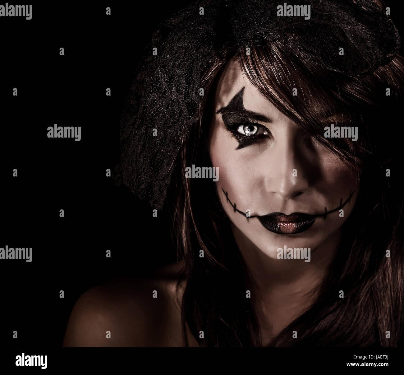 Furchterregende Hexe Porträt isoliert auf schwarzem Hintergrund, attraktive Frau mit unheimlich Make-up, Halloween Stockfoto