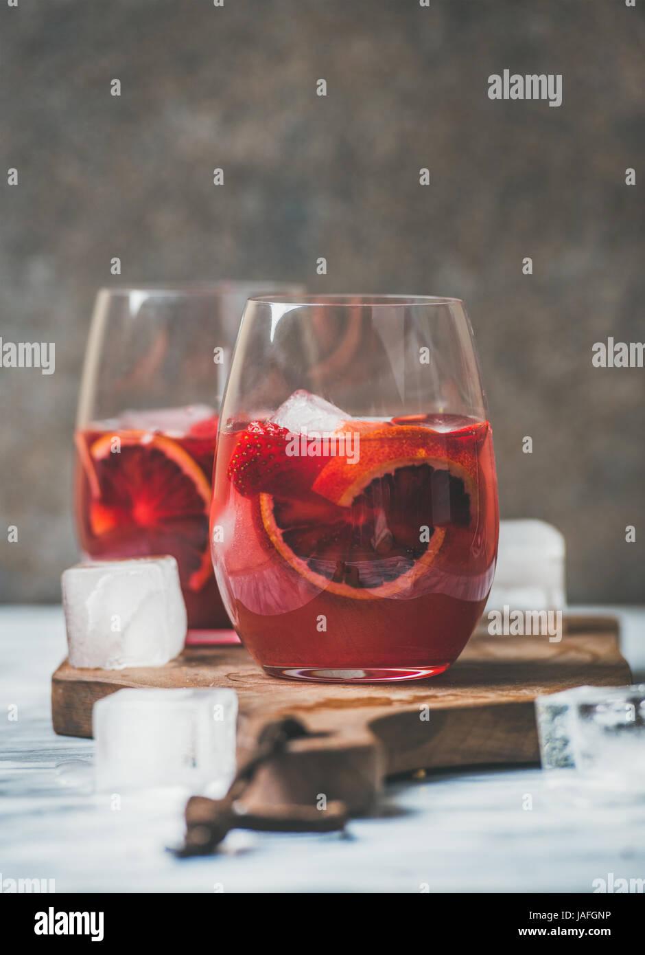 Blutorange und Erdbeere Sommer Sangria. Frucht, erfrischende rose Wein Cocktails in Gläser mit Eis, dunklen Hintergrund, Stockfoto