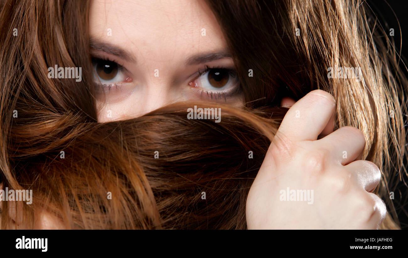 Close-up Portrait einer schönen Frau bedeckt das Gesicht mit langen braunen Haaren Stockfoto