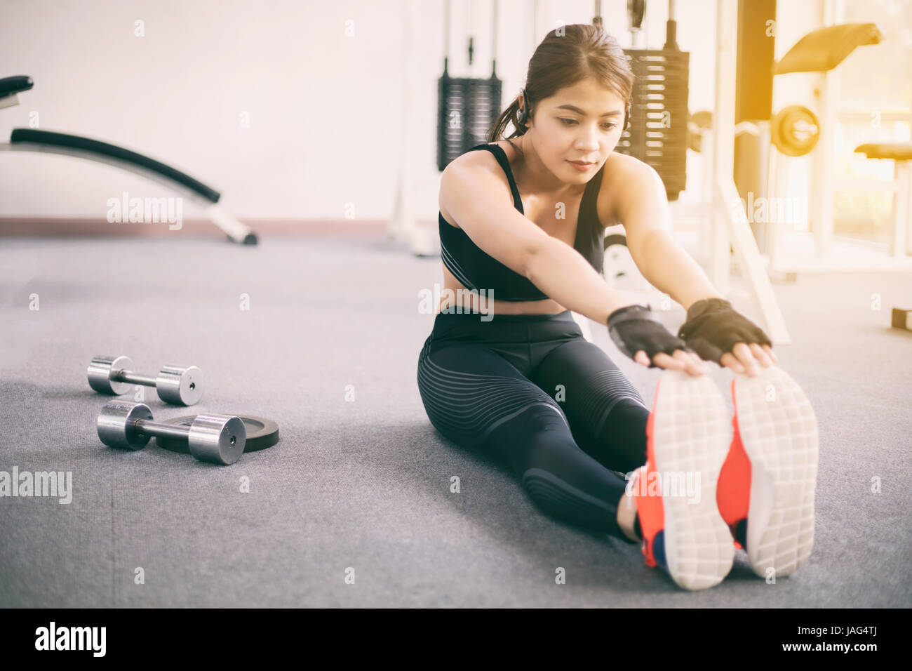 Sportliche Frau asiatischen Aufwärmen und junge Sportlerin auf eine Ausübung sitzen und erstreckt sich Stockbild