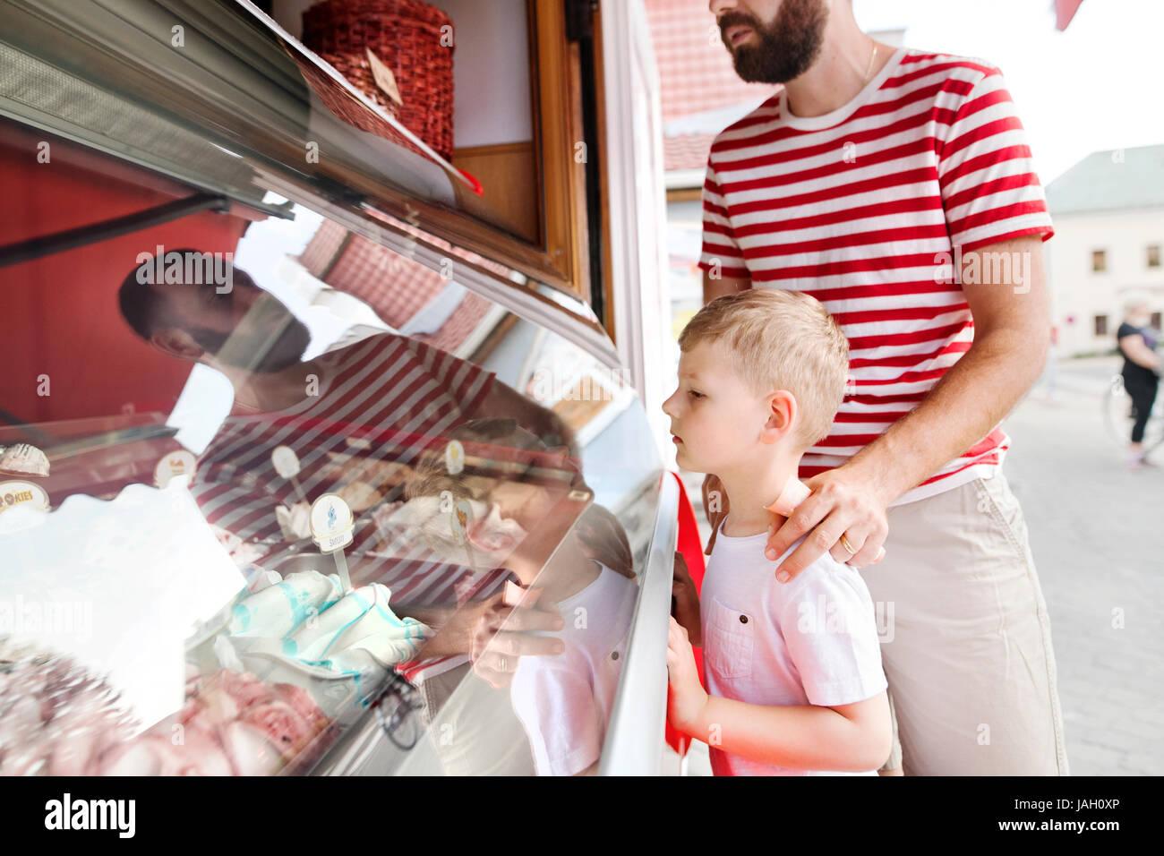 Junger Vater und seinen kleinen Sohn Eis zu kaufen. Sonniger Tag. Stockbild