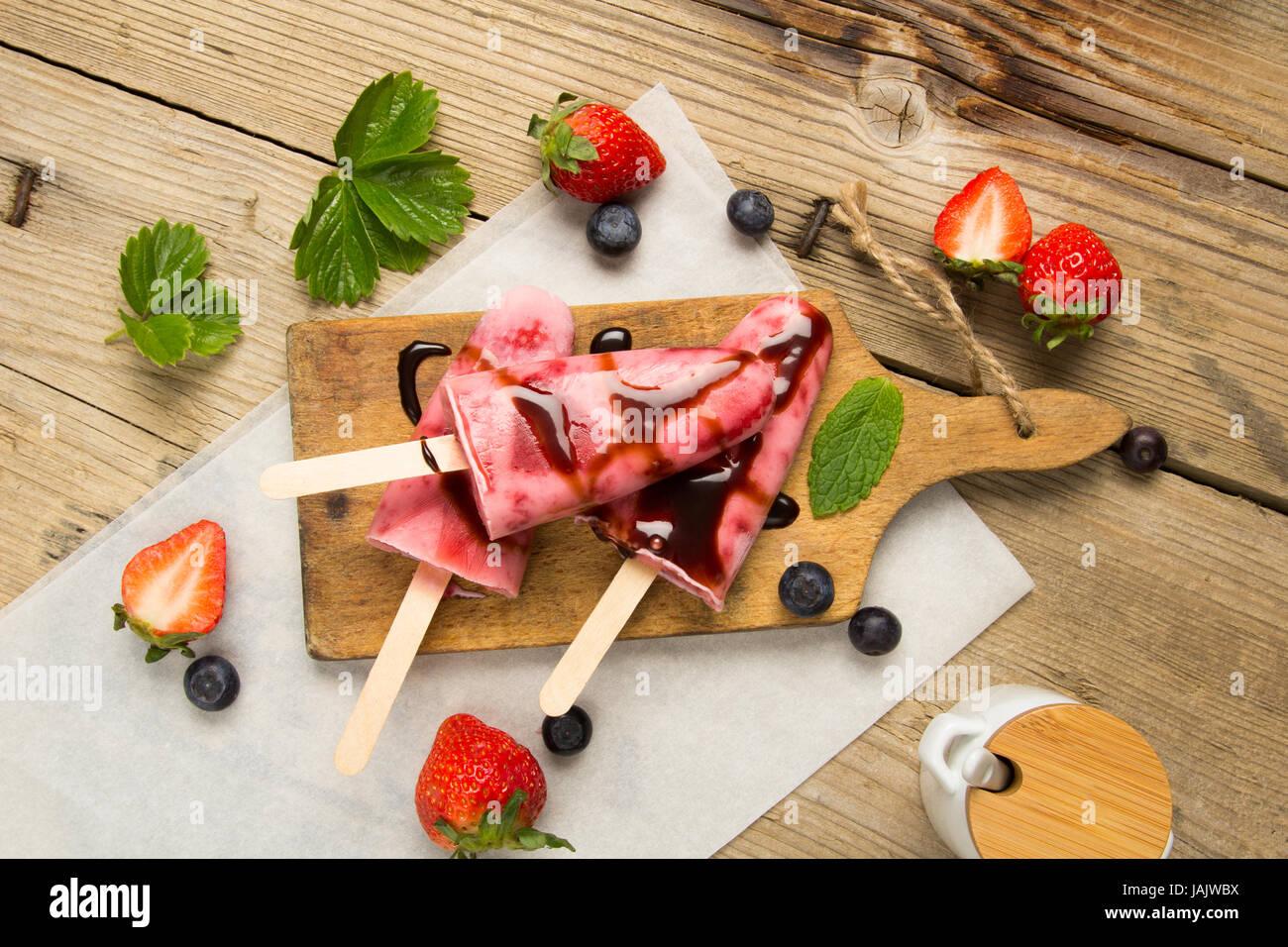 Frische hausgemachte Erdbeereis auf hölzernen Hintergrund. Bio, Vegan Eis am Stiel und Schokoladensauce Stockfoto