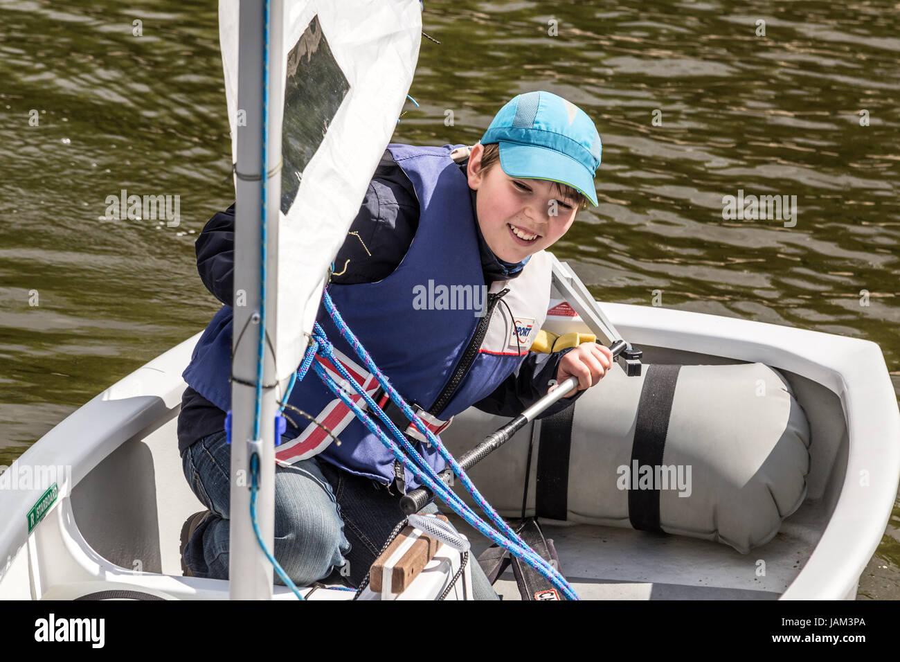 Junge - Matrose auf Optimist Klasse Segelboot nach Regatta Rennen. Stockbild