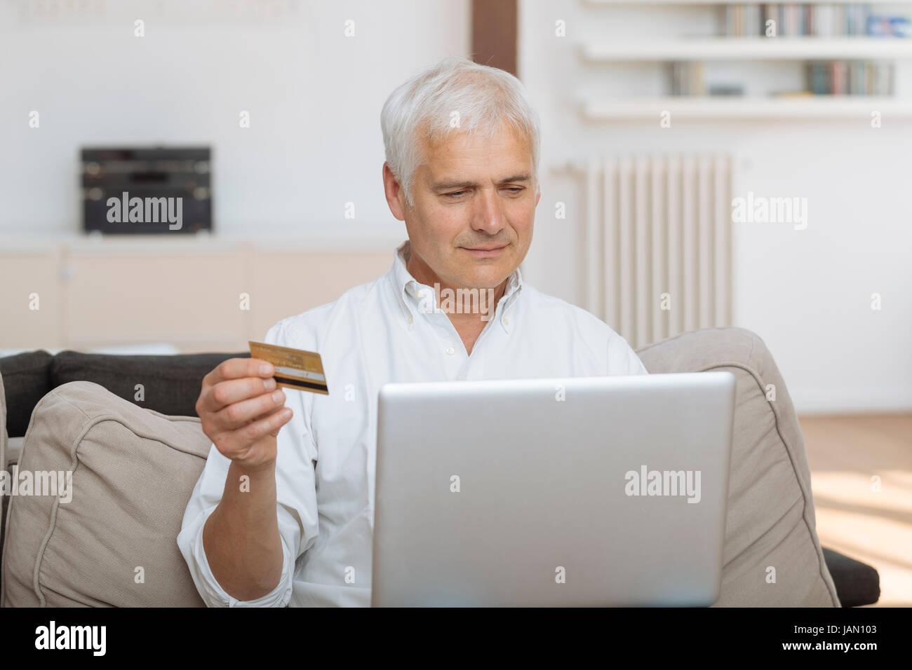 reifer Mann mit seinem Laptop und hält seine Kreditkarte Stockbild