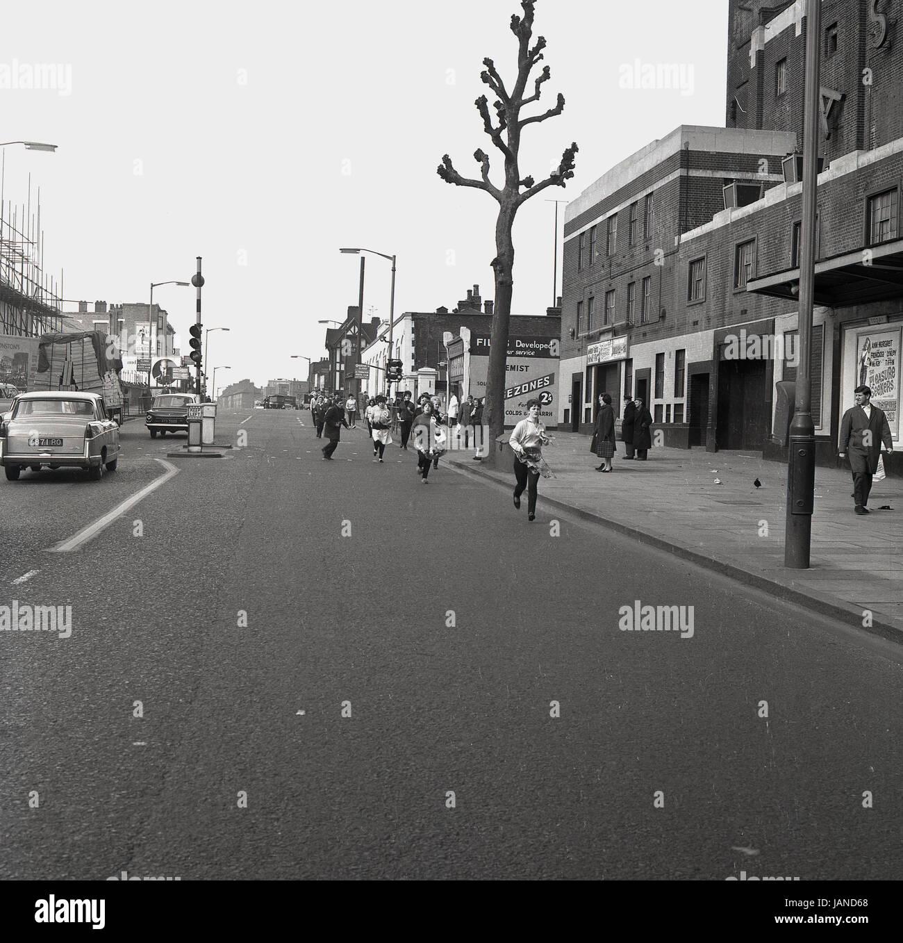 1965, historische, Bild zeigt eine Reihe von Damen der Old Kent Road, Peckham, London, mit Pfannen und Schürzen Stockbild