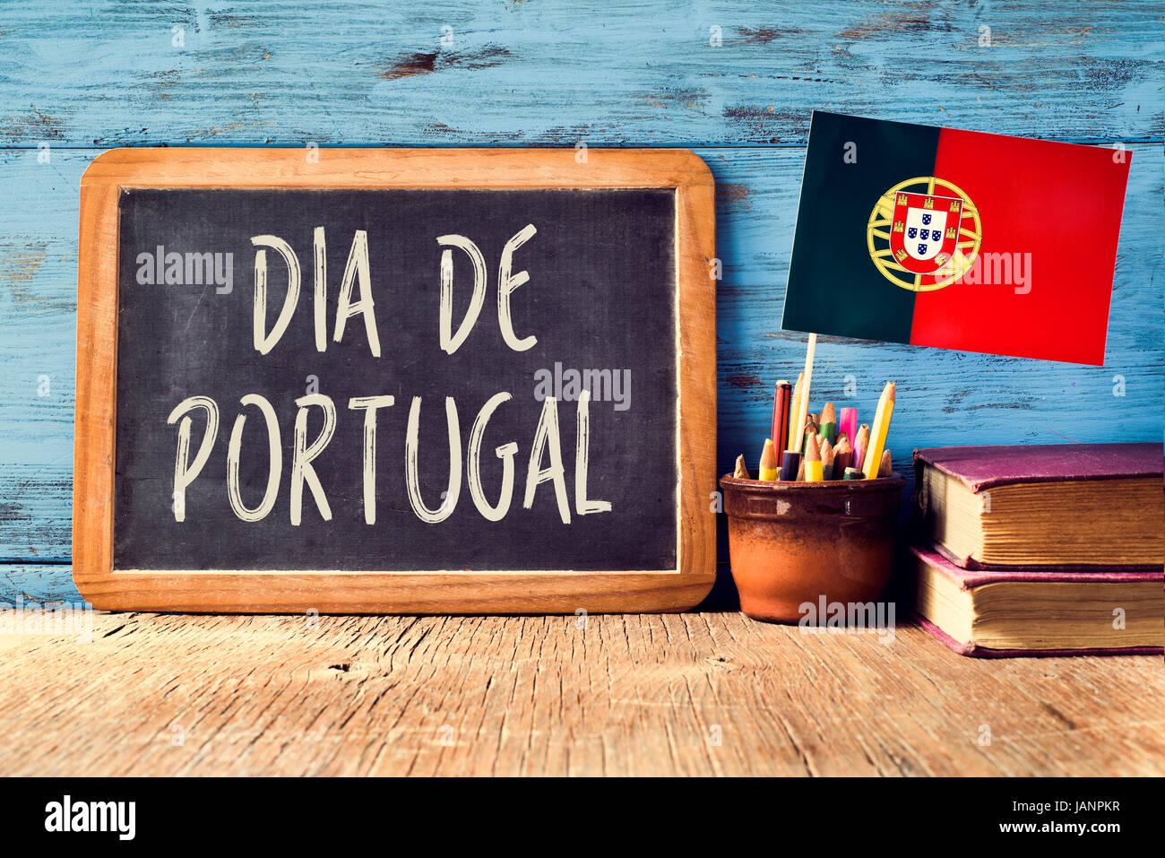 der Text Dia de Portugal, Portugal-Tag in eine Tafel und eine Flagge von Portugal, auf einem rustikalen Holztisch Stockbild
