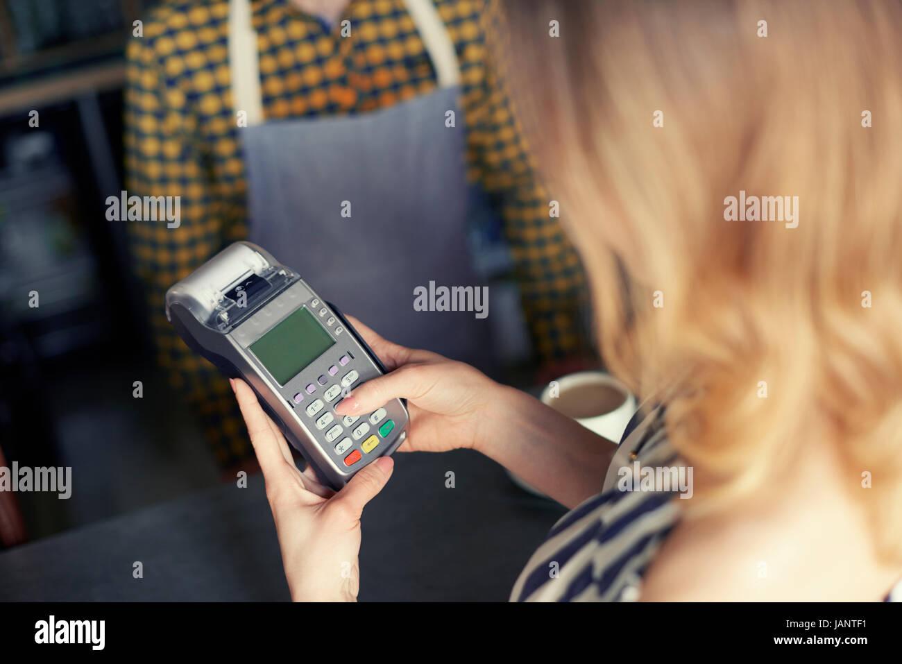 Kunden mit Pin Eingabe Kreditkartenleser Stockfoto
