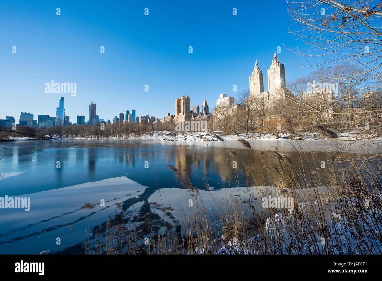 Malerische Aussicht auf die Upper West Side-Skyline reflektiert im Eis der zugefrorenen Central Park-See nach einem Stockbild