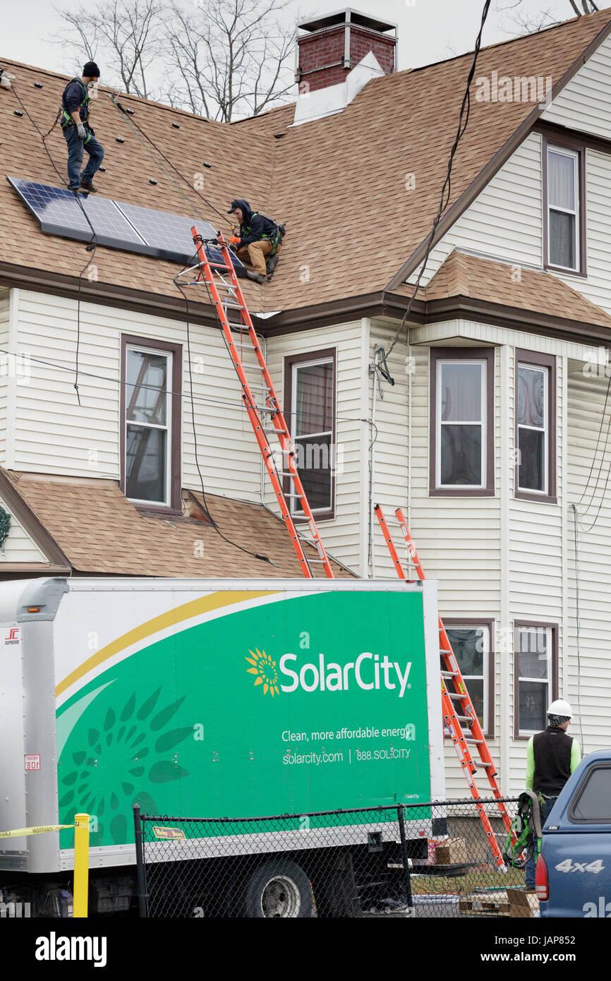 Amsterdam, New York ? 20. Januar 2017: Arbeiter installieren Sonnenkollektoren auf dem Dach in der Stadt Montgomery Stockbild