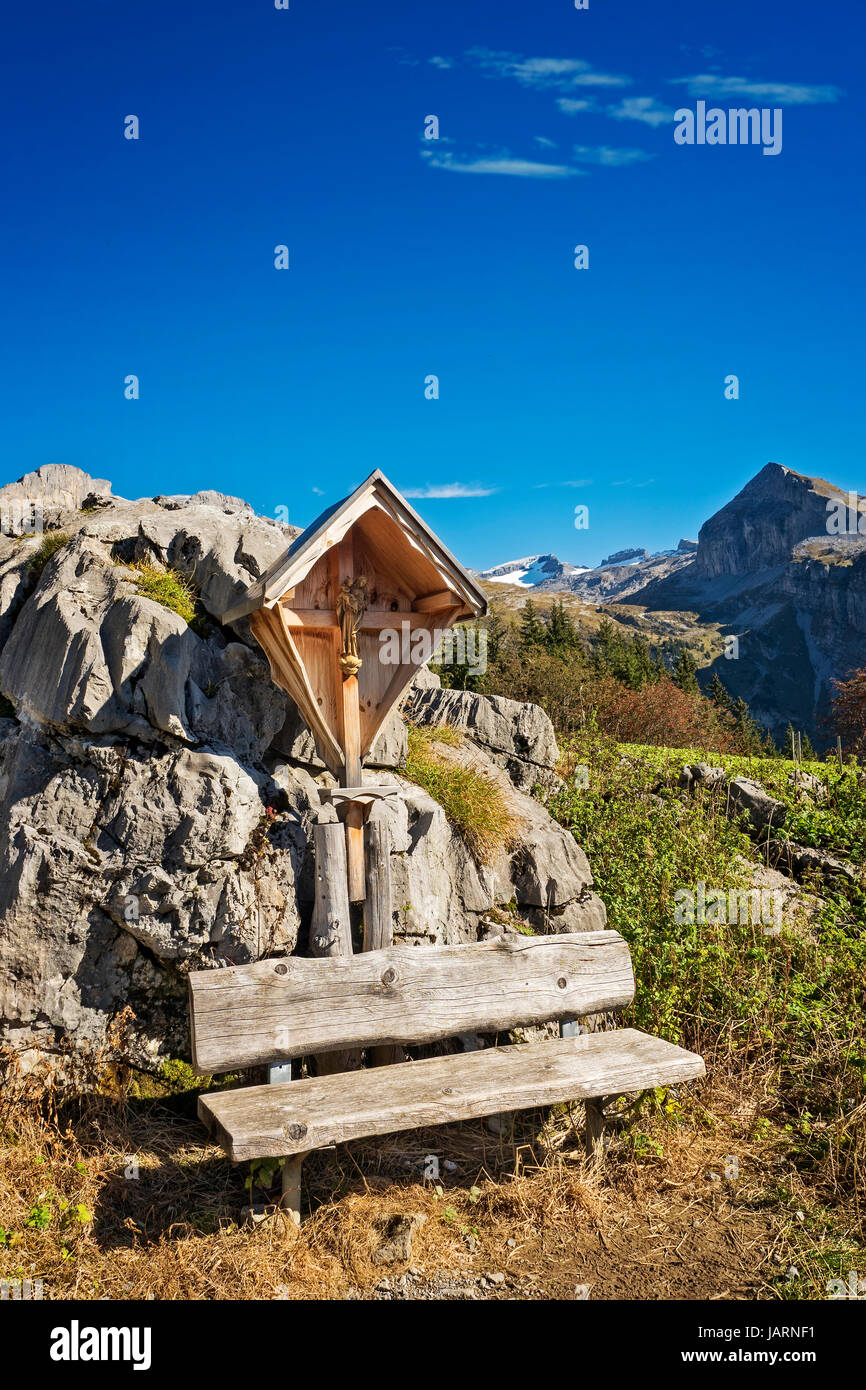 Holzbank vor der Bildstock Kreuz, blauer Himmel, Blick über Berge, Schweizer Alpen Stockbild