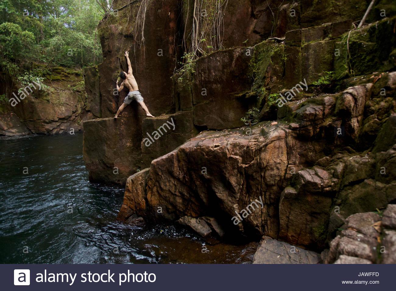 Ein Mann tut Tiefenwasser free solo auf den Klippen in die Schlucht hinunter Riam Parit, oder der Kanal Wasserfall, Stockbild