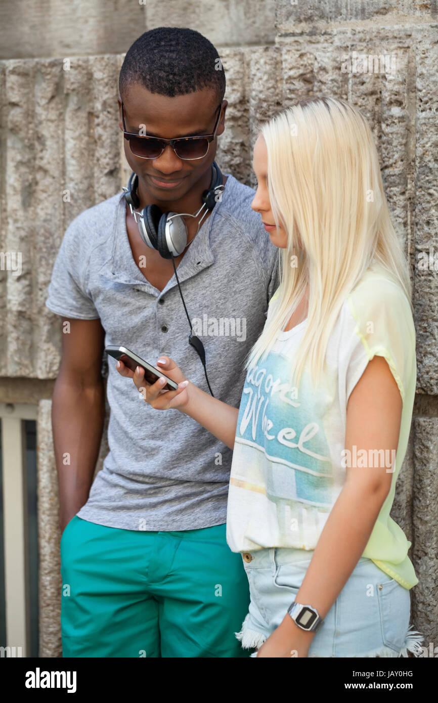Lachende Junge Freunde Im Sommer in der Stadt Mit mobiltelefon Stockfoto