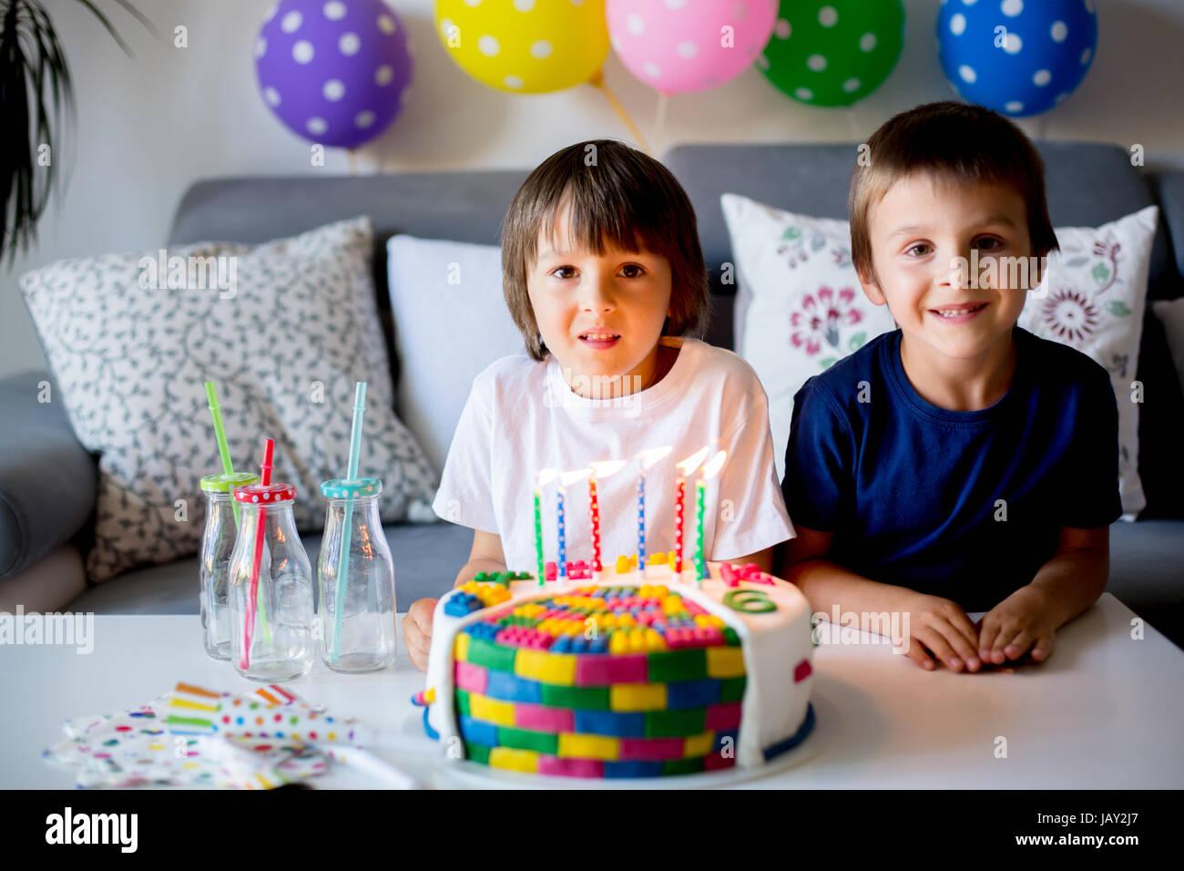 Süßes kleines Kind und sein Bruder, feiert seinen sechsten Geburtstag, Kuchen, Luftballons, Kerzen, Cookies. Stockbild