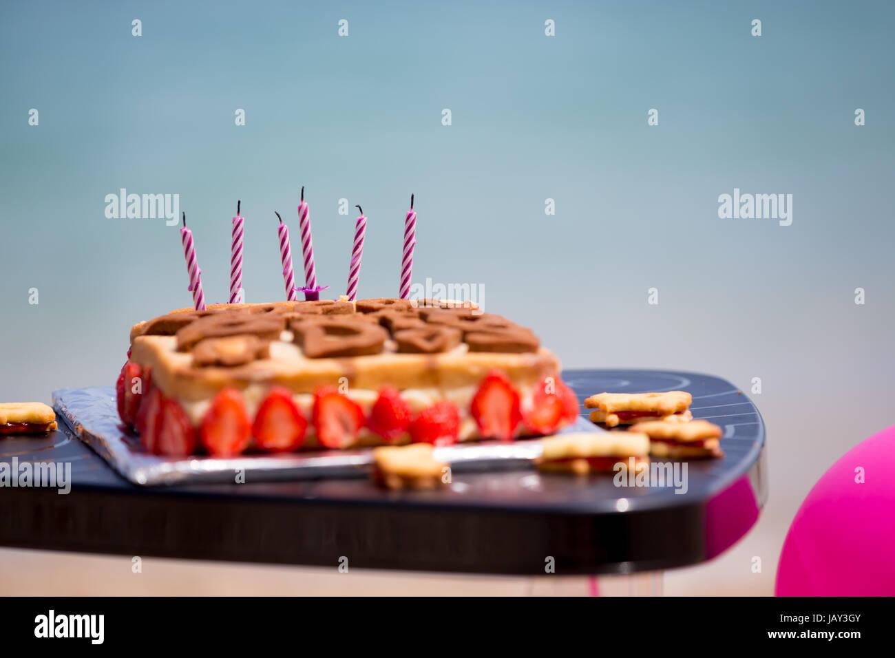 Birthtday Kuchen mit Kerzen und Cookies am Strand, Luftballons Stockbild