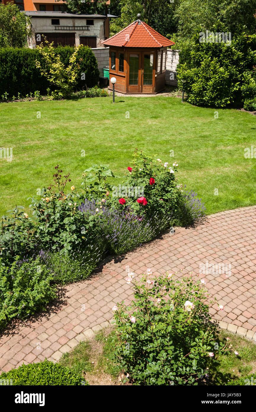 Schöner Garten Mit Blühenden Rosen, Ziegelsteinweg Und Einem Kleinen  Pavillon