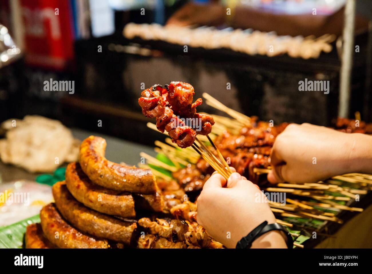 CHIANG MAI, THAILAND - 27 AUGUST: Mann kauft gegrilltes Schweinefleisch am Spieß auf dem Sonntagsmarkt (Walking Stockbild
