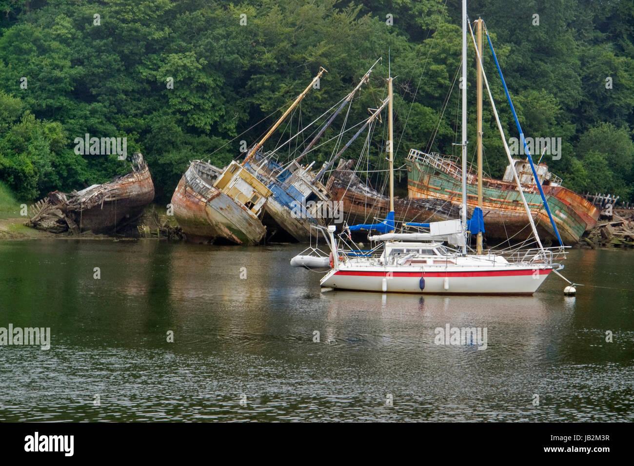 Schiffswracks und Boot auf einem Fluss in der Bretagne, Frankreich Stockbild