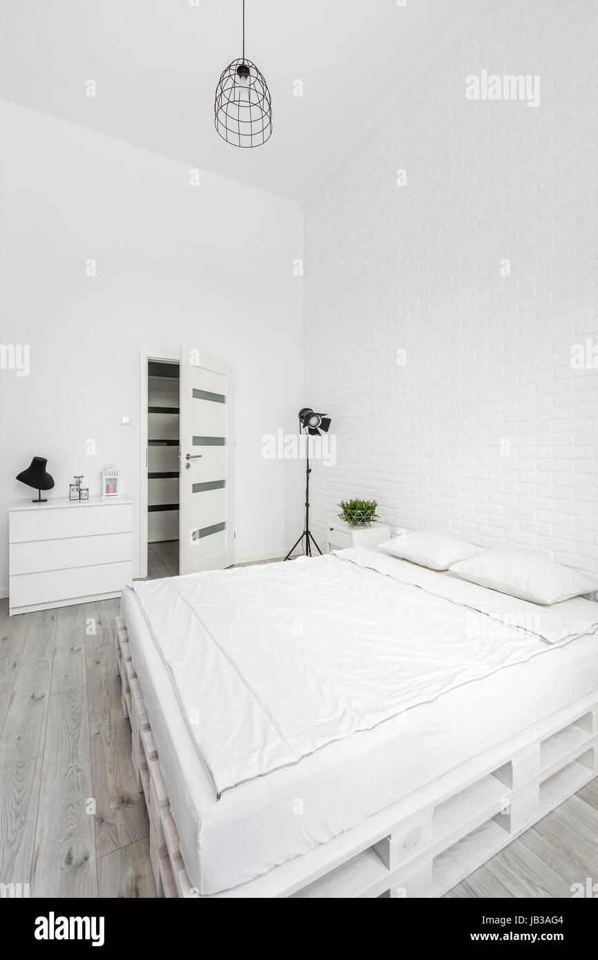 weißes schlafzimmer mit palette bett, mauer und metall lampe