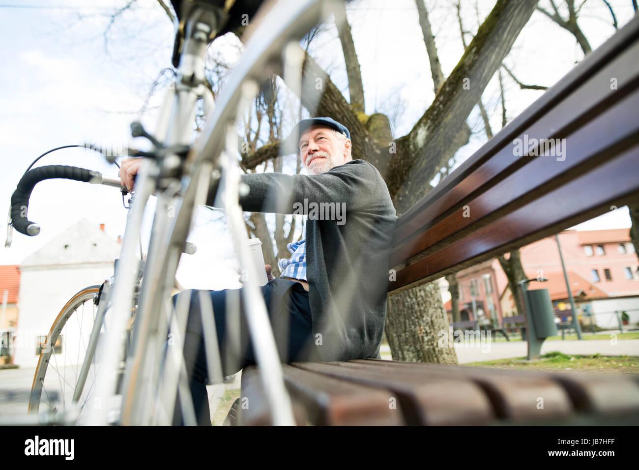 Ältere Mann mit Fahrrad in der Stadt, sitzen auf Bank mit Kaffee Stockbild