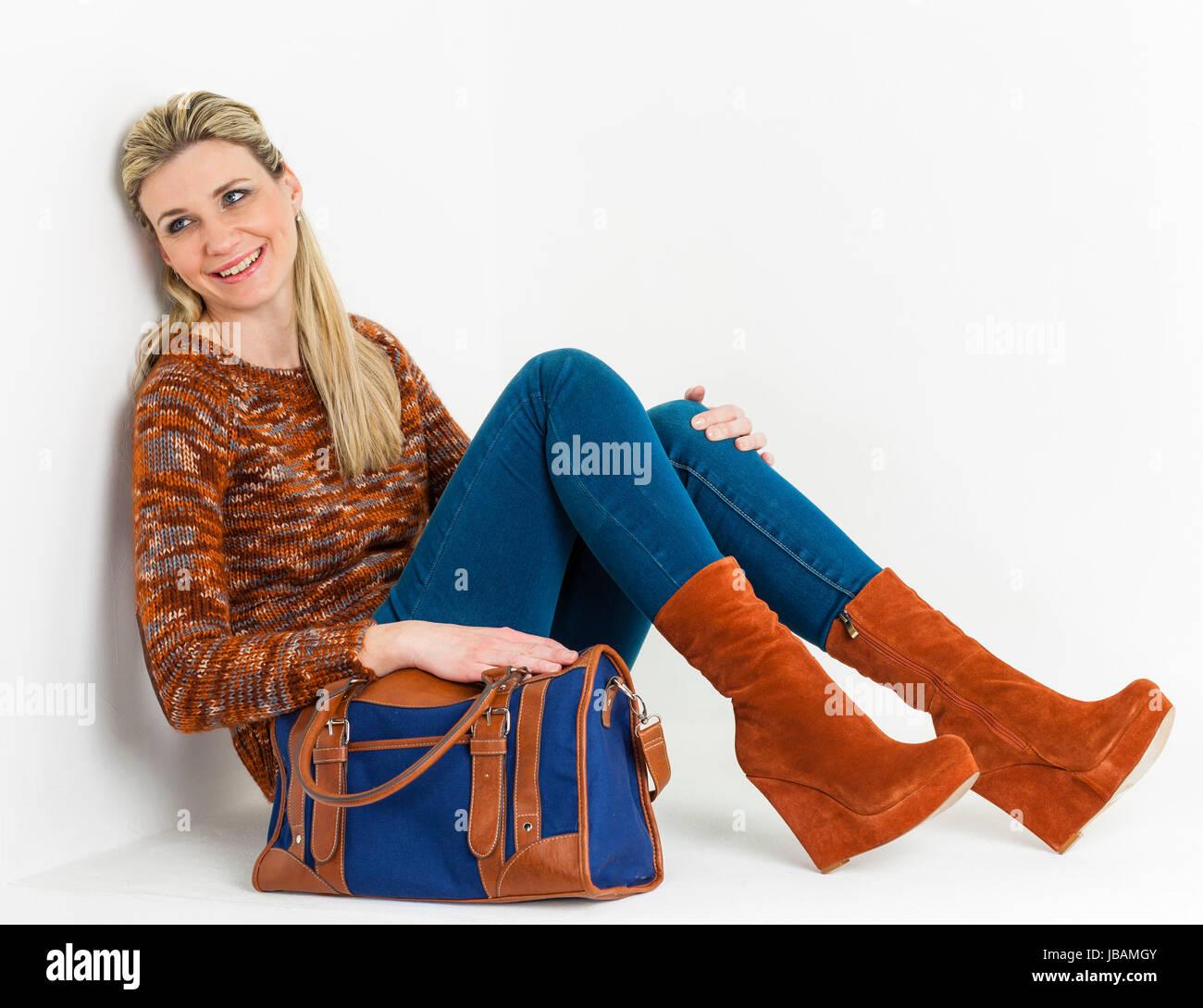 76a3f8ec02 sitzende Frau Braun modische Plateau-Schuhe mit einer Handtasche tragen