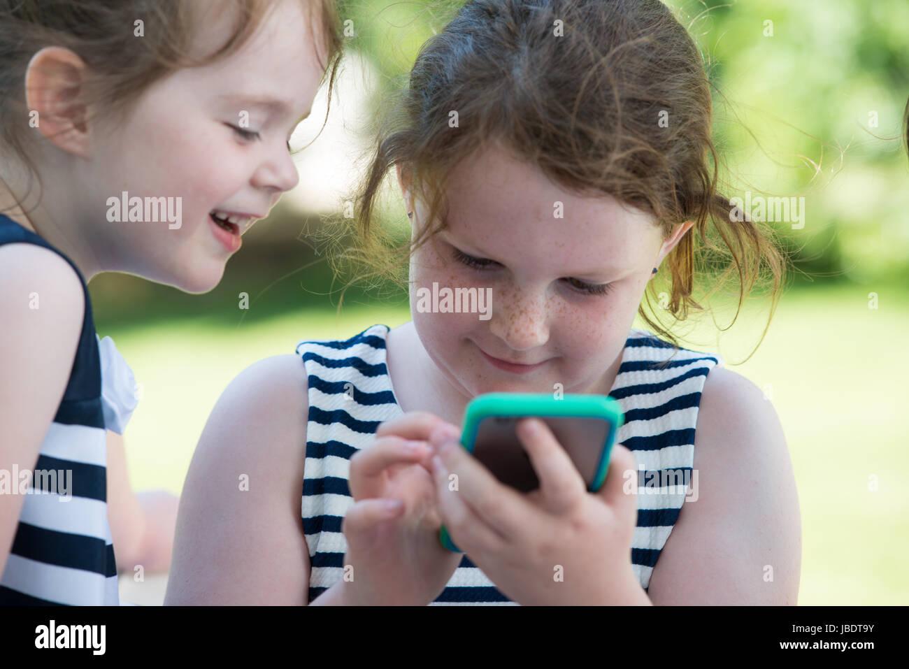 Glücklich lachende Kinder spielen mit Smartphone außen Stockbild