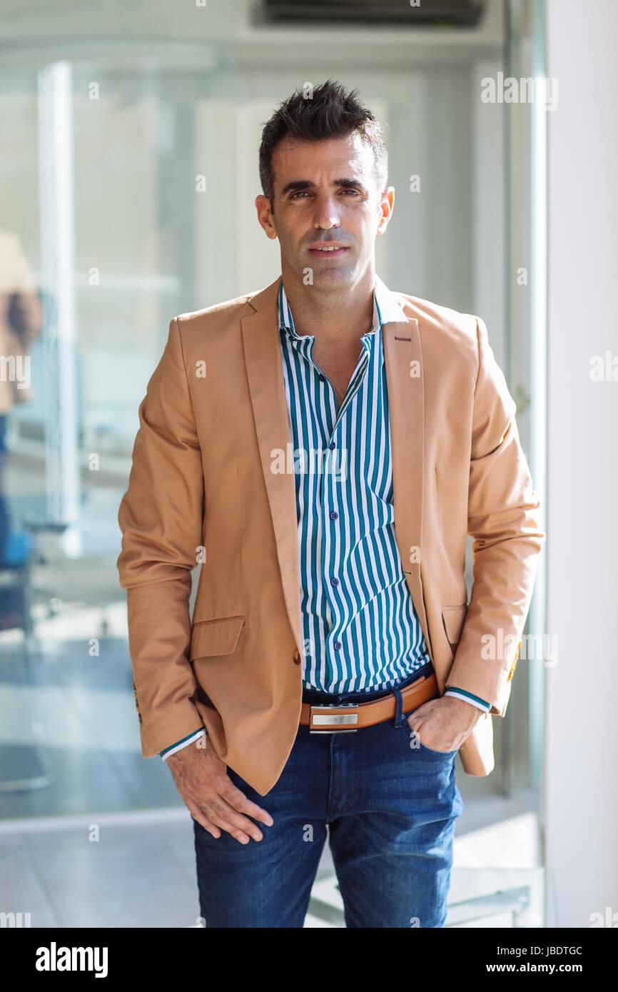 Ein 35-40 Jahre alte Mann kaukasischen dunkle Haare cool modernes Aussehen mit Hand in der Tasche in eine abgespeckte Stockbild