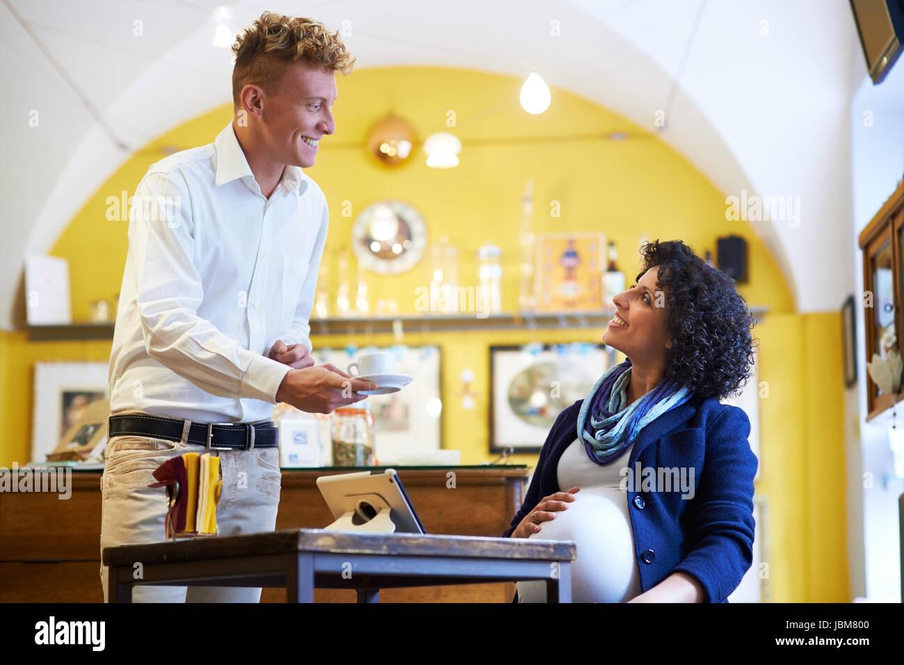 Menschen in Cafeteria mit Barkeeper servieren Espresso Kaffee, schwanger Geschäftsfrau mit Ipad am Tisch sitzen Stockfoto