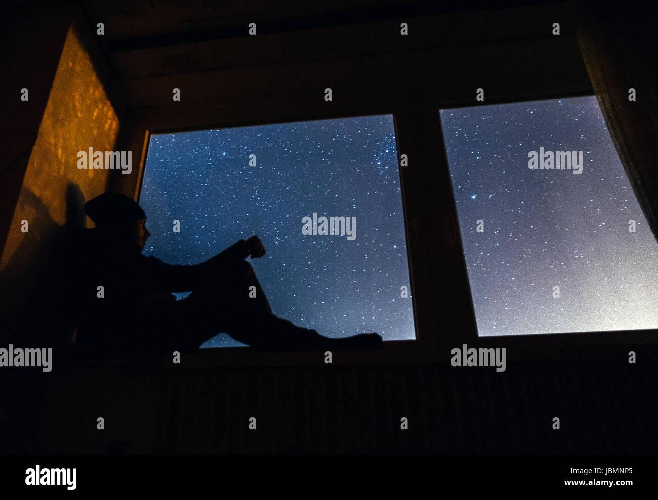 Mann sitzt im Fenster in der Nacht Stockbild