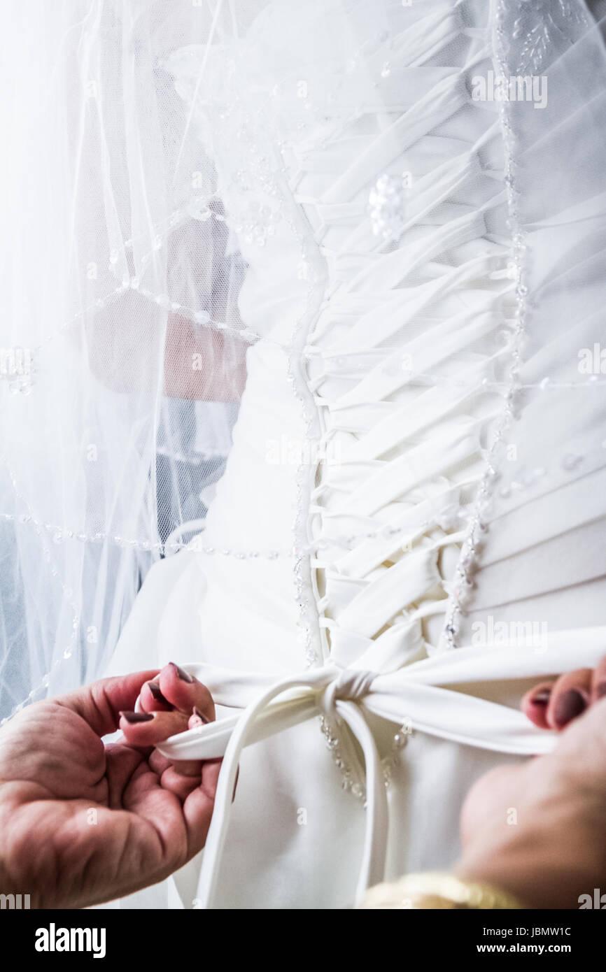 Mutter binden der Schnürsenkel zurück, der Braut Hochzeit Kleid ...