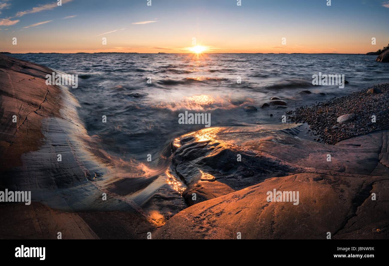 Malerische Landschaft mit Sonnenuntergang und Meer am Sommerabend in Finnland Stockbild