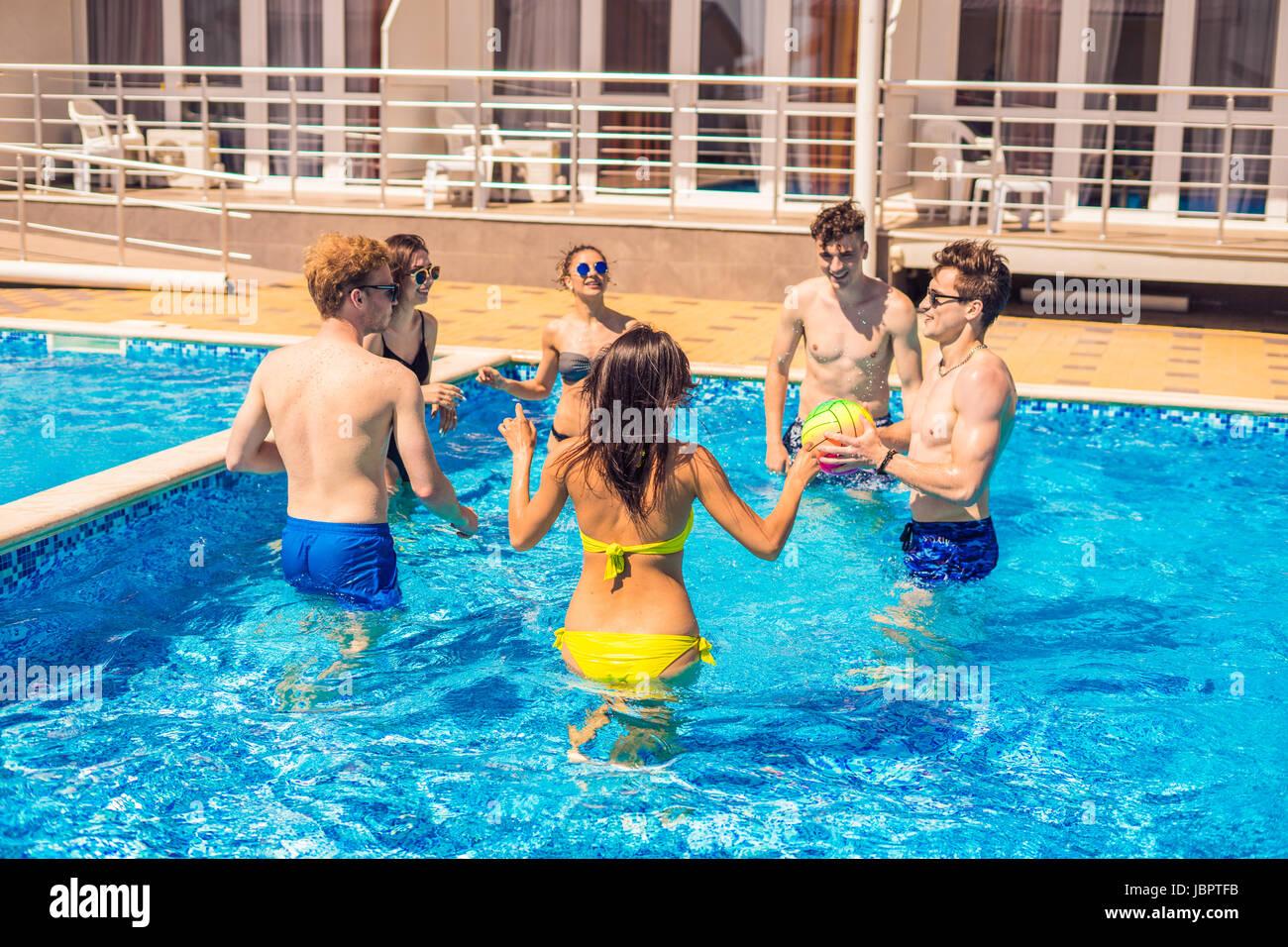Gruppe von fröhlichen Paare Freunde Wasservolleyball spielen Stockbild