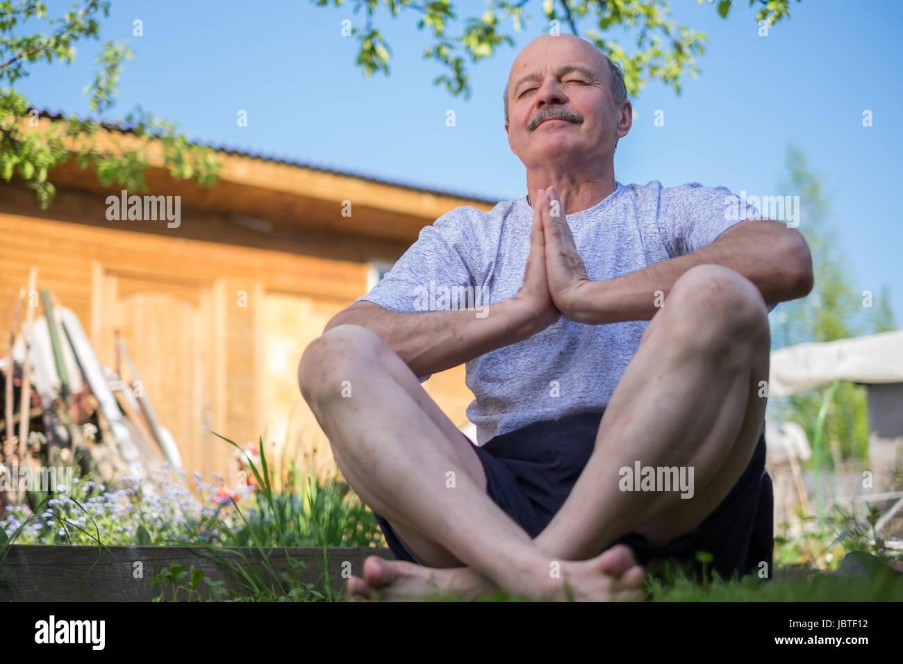 Ältere Mann mit Schnurrbart mit Namaste sitzen. Konzept der Ruhe und Meditation. Stockbild