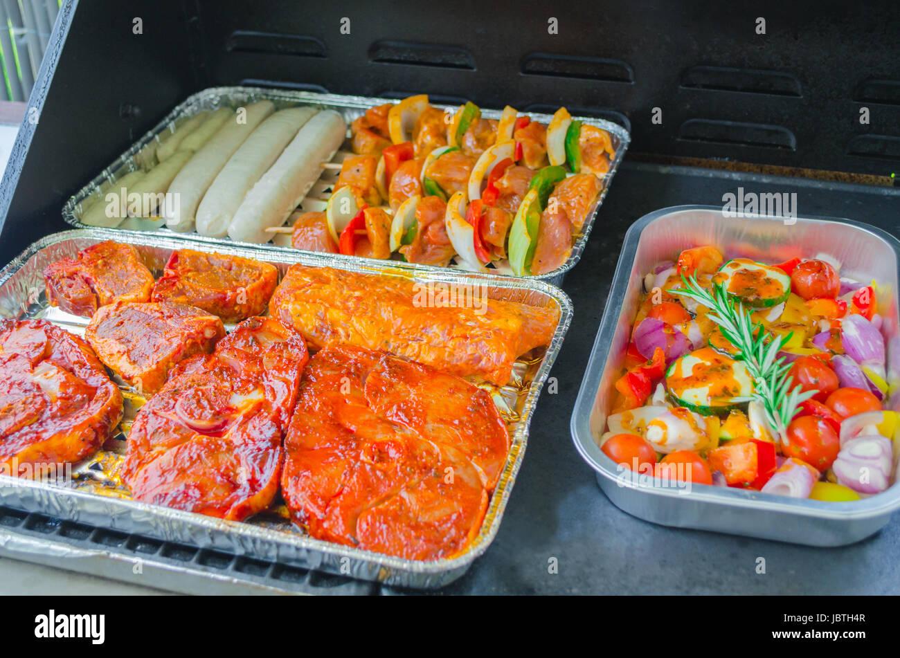 grillgut, grillfleisch mariniert in einer aluschale auf einem grill