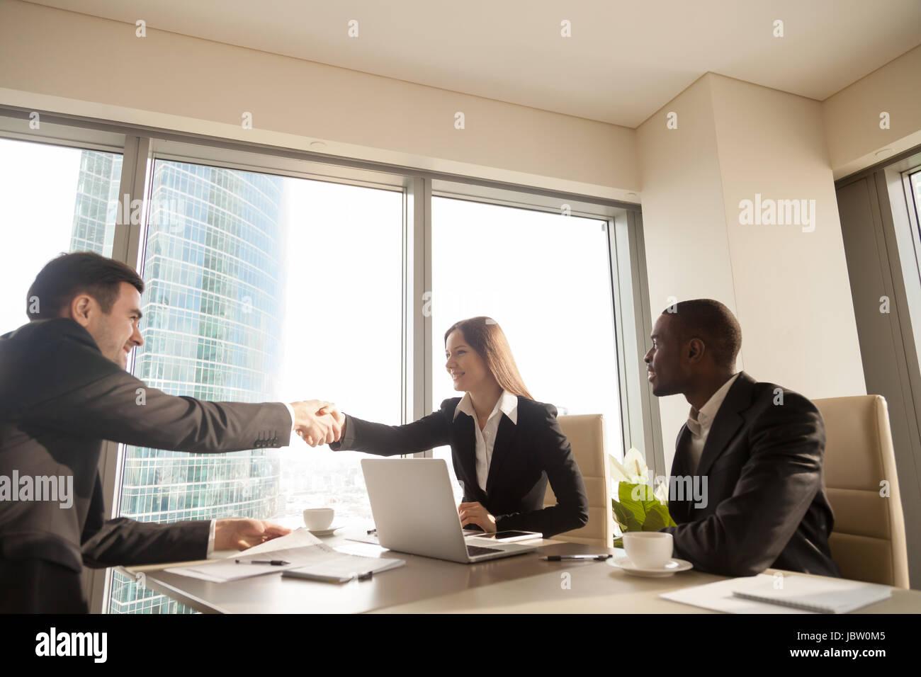 Fröhliche weiblichen und männlichen kaukasischen Partner Handshake über Schreibtisch, multiethnischen Stockbild