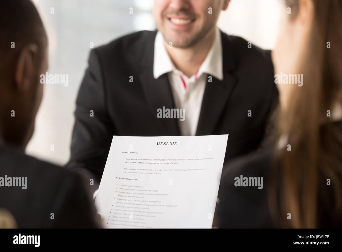 Nahaufnahme von Arbeitgeber oder Personalvermittler halten überprüfen Lebenslauf glücklich lächelnd Stockbild