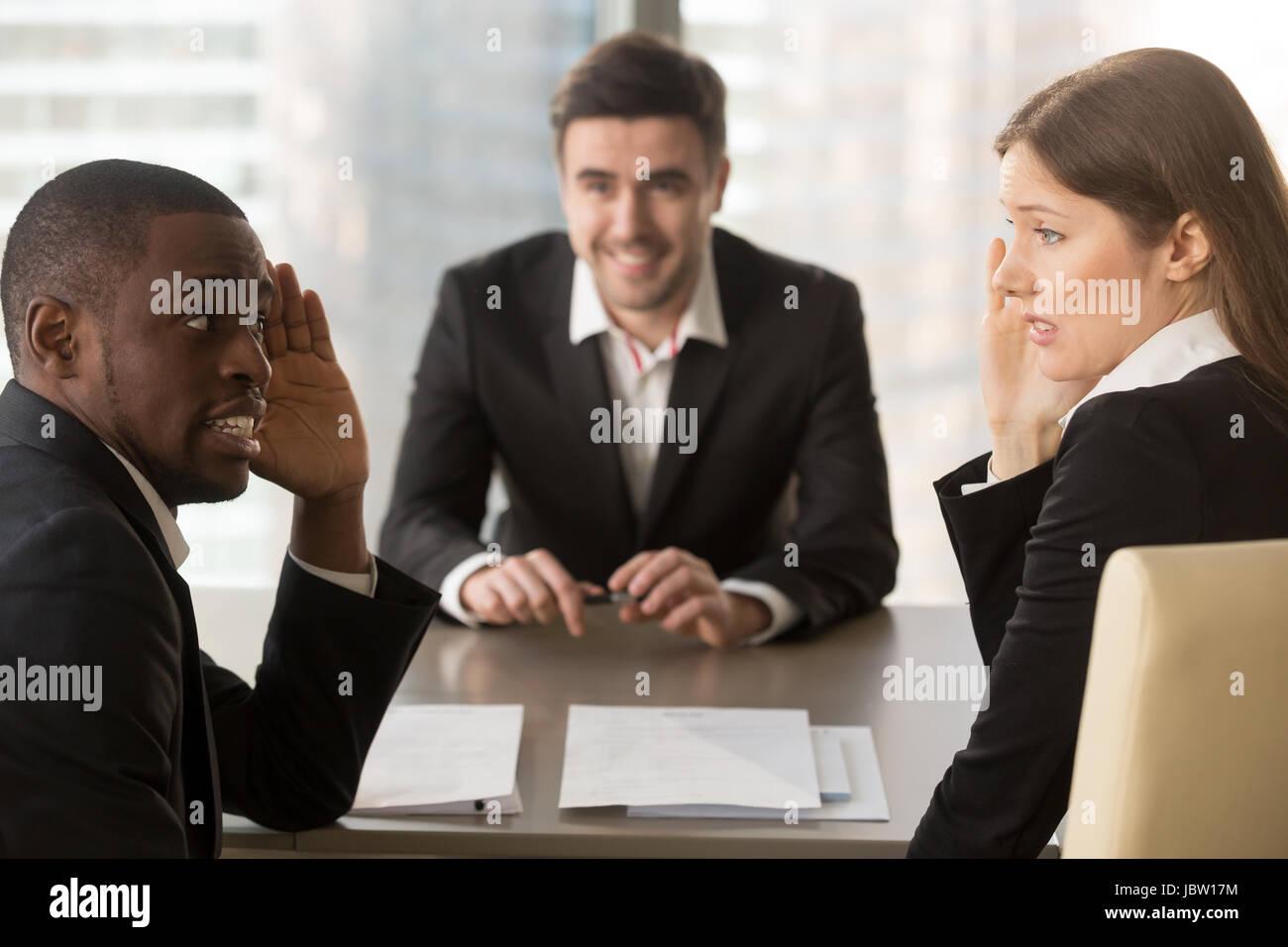 Gemischtrassig verwirrt Arbeitgeber heimlich diskutieren Stellenbewerber, verdeckt Gesicht mit Händen, verwirrten Stockbild