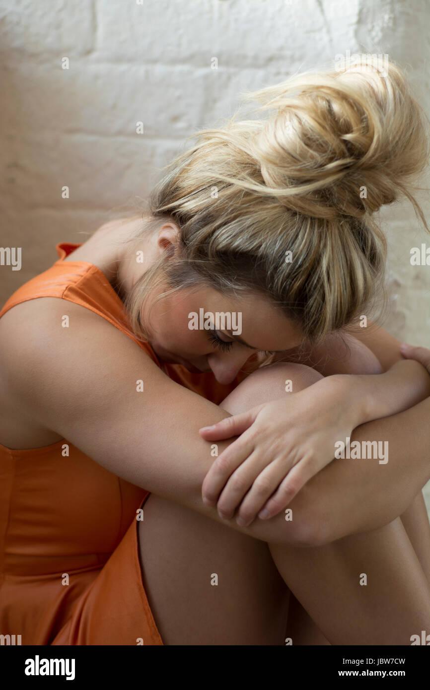 Miserable junge Frau sitzen Stockbild