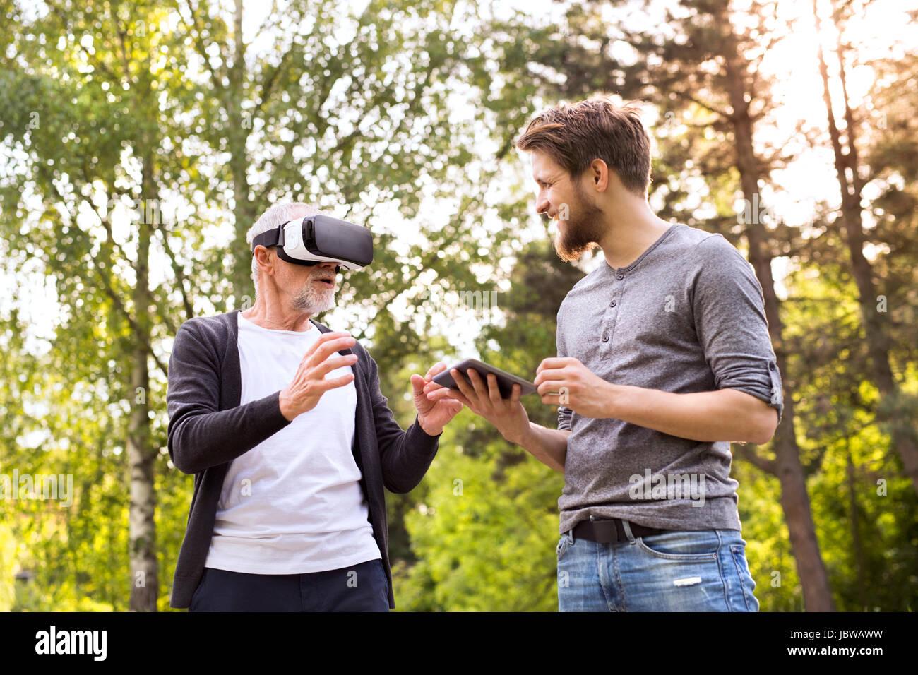 Junger Mann und Vater senior mit VR-Brille im Freien. Stockfoto