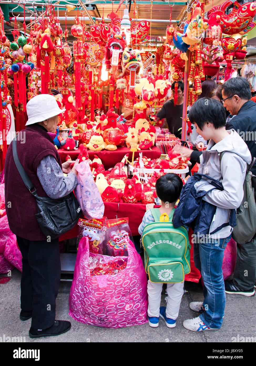 Vertikale Ansicht einer Familie Wahl Chinese New Year Verzierungen an einem Marktstand in Hong Kong, China. Stockbild