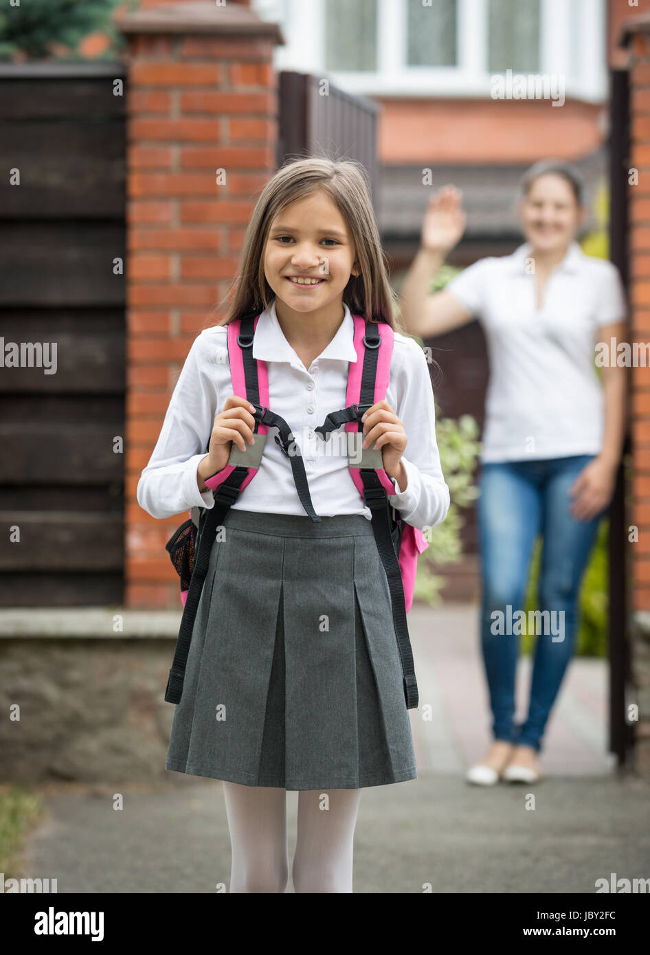 Mutter im Türrahmen stehen und winken für ihre Tochter zur Schule zu ...