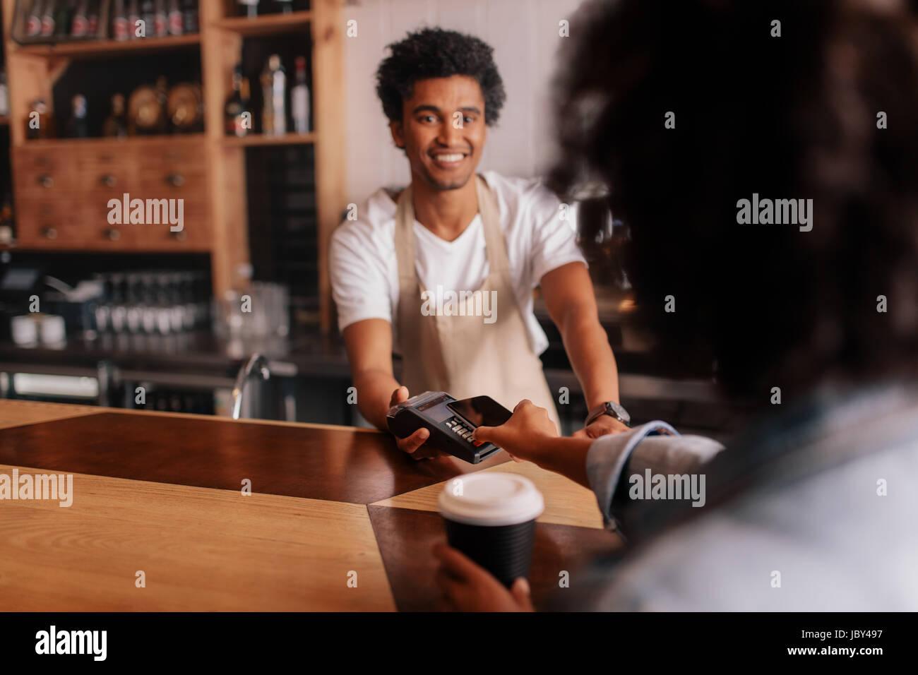Weibliche Kunden, Zahlung per Handy am Schalter im Café mit jungen Mann. Barista Holding Kreditkarte lesen Maschine Stockfoto