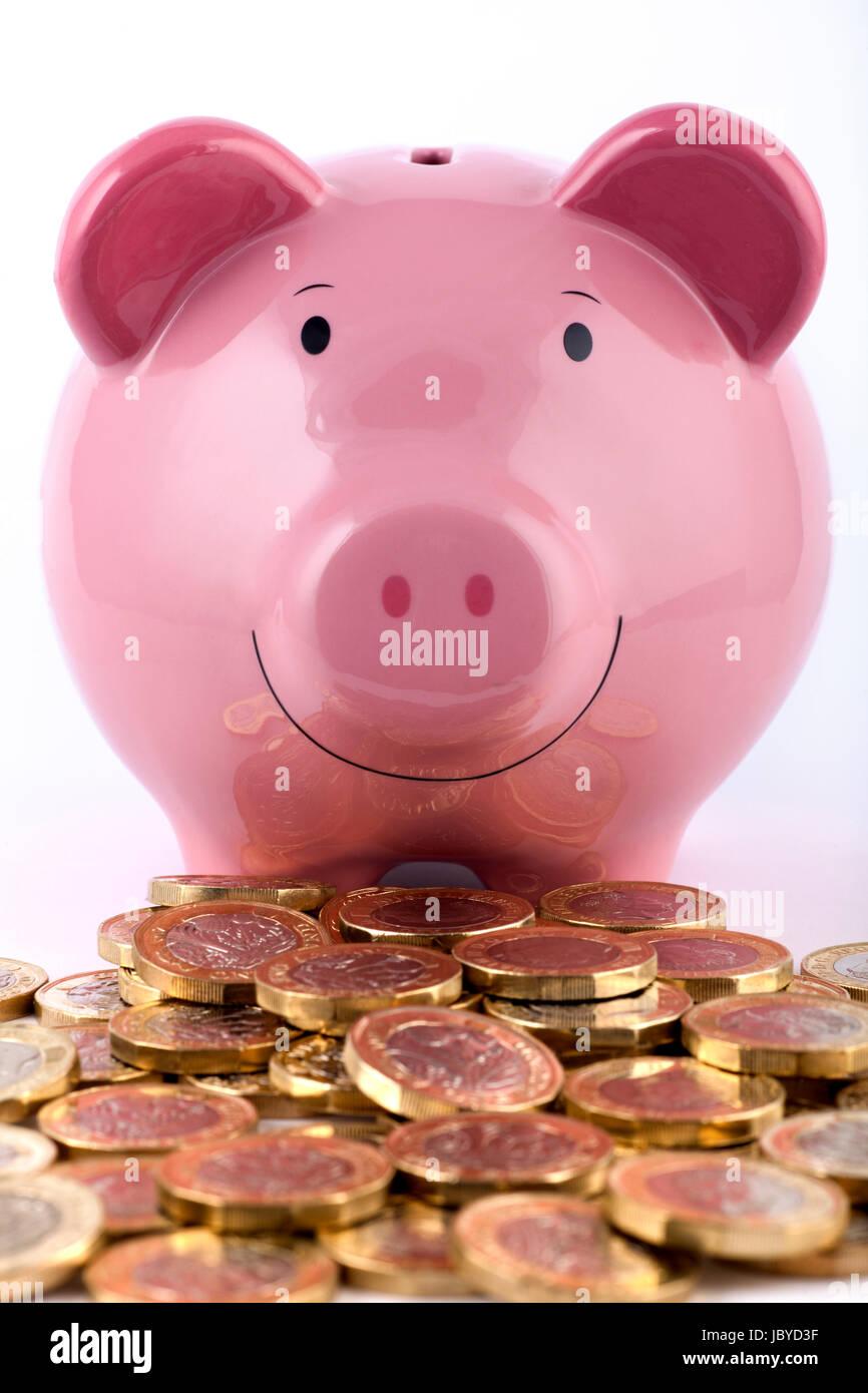 Sparschwein mit einem Haufen neuer 2016/2017 ein Pfund-Münzen. Stockbild