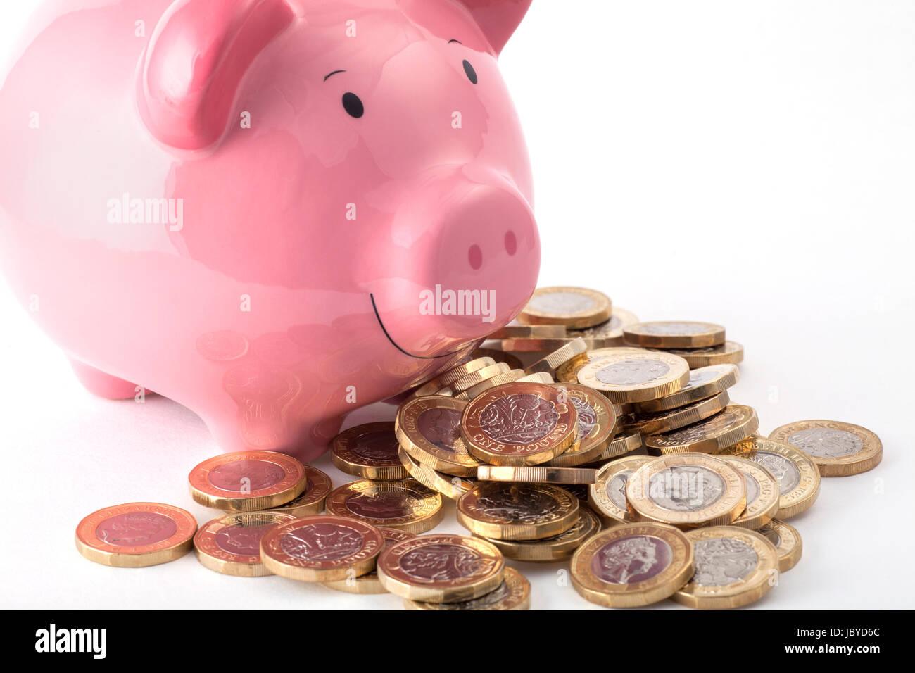 Sparschwein mit einem Haufen neuer Pfund-Münzen Stockbild