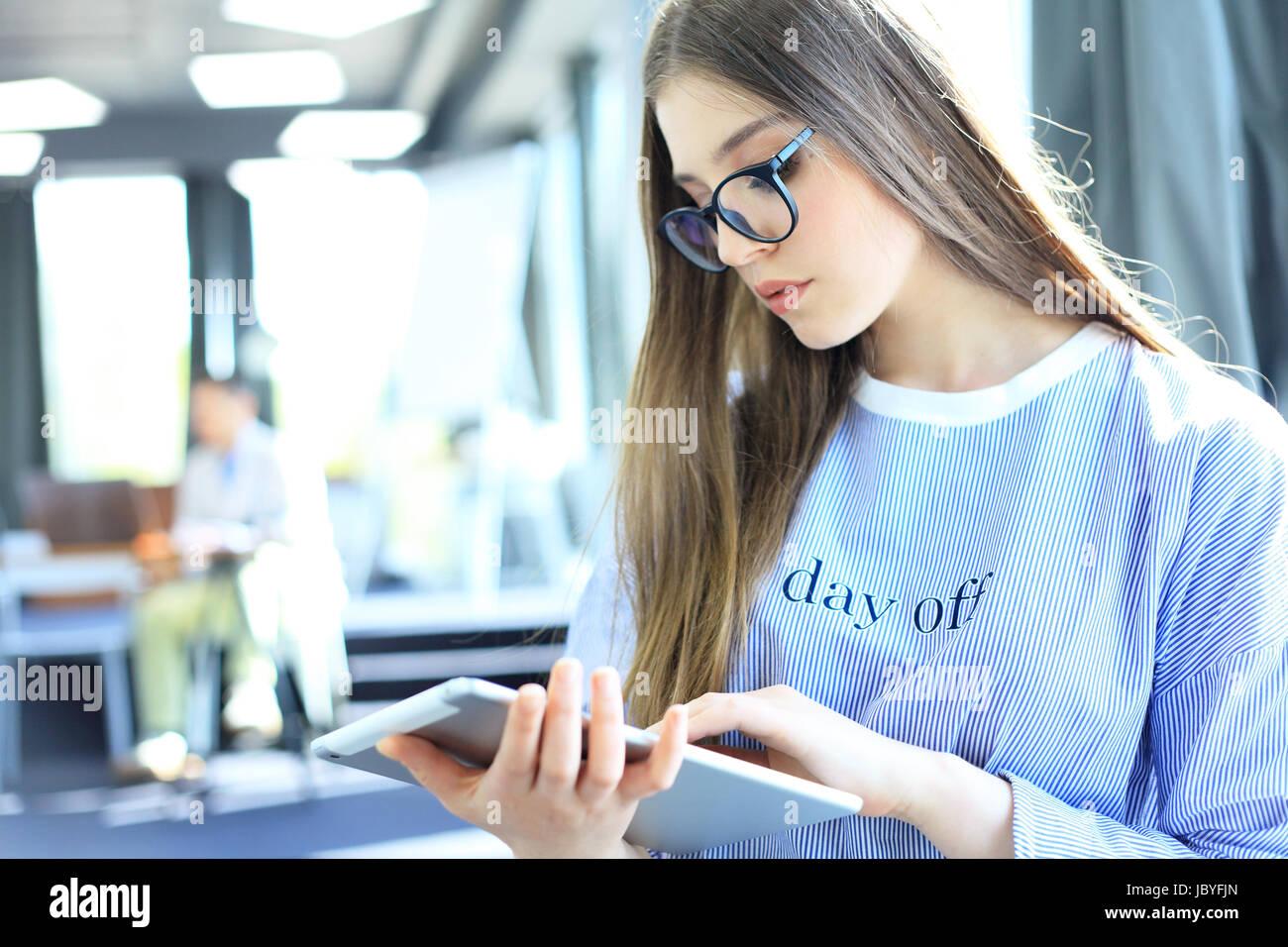 Attraktive Geschäftsfrau, die auf einem digitalen Tablet im Büro arbeiten Stockbild