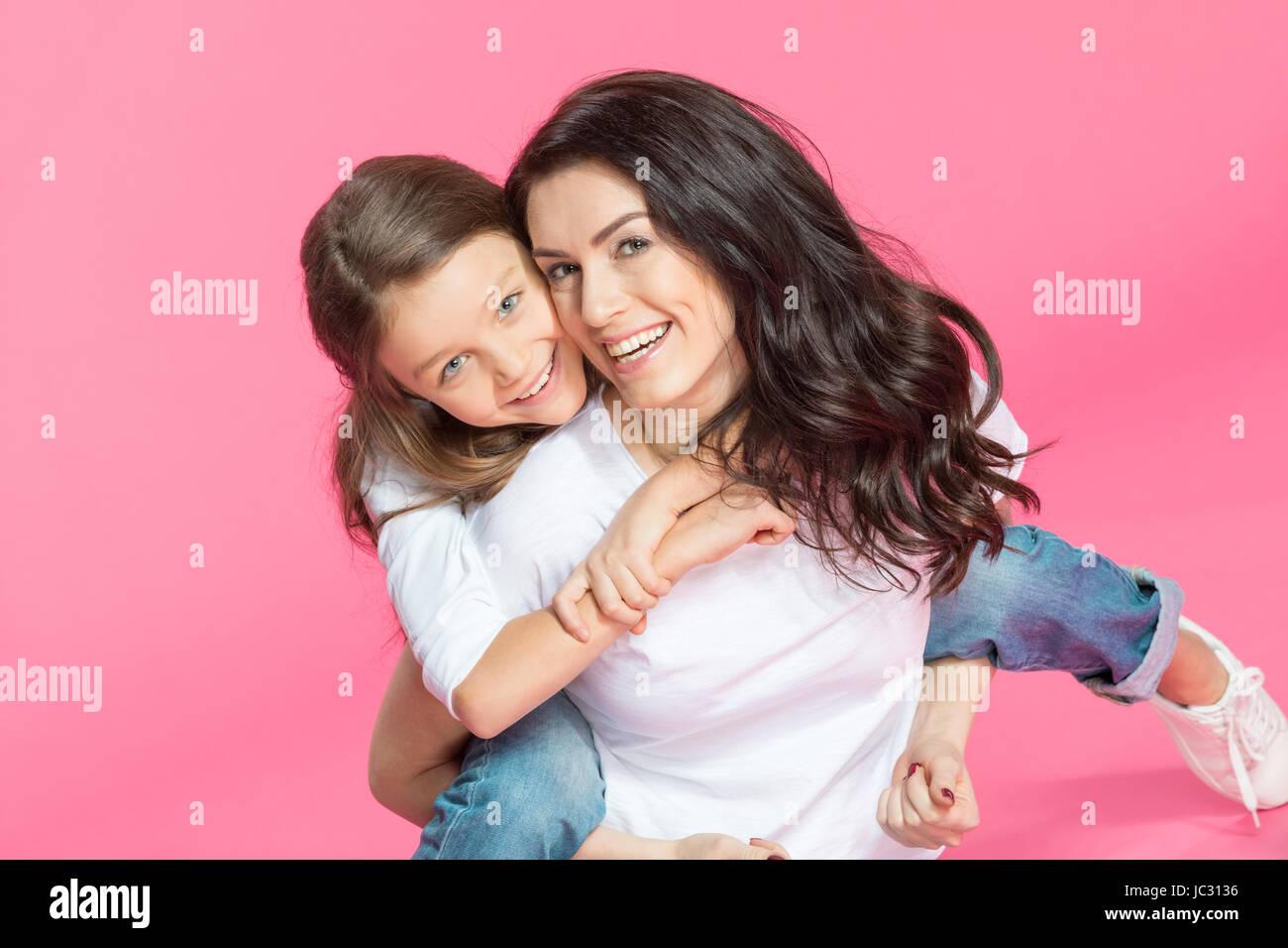 Glückliche schöne Mutter und Tochter umarmt und lächelt in die Kamera Stockbild