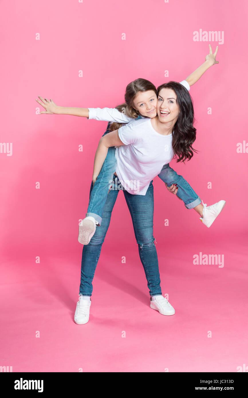 Glückliche Mutter Huckepack entzückende kleine Tochter mit offenen Armen auf rosa Stockbild