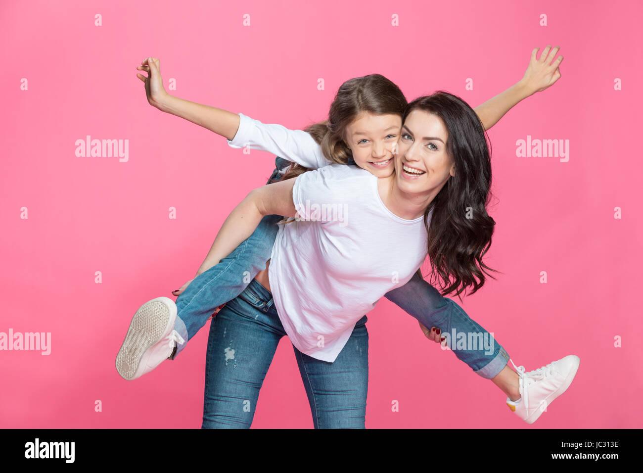 Glückliche Mutter Huckepack entzückende kleine Tochter lächelnd in die Kamera Stockbild