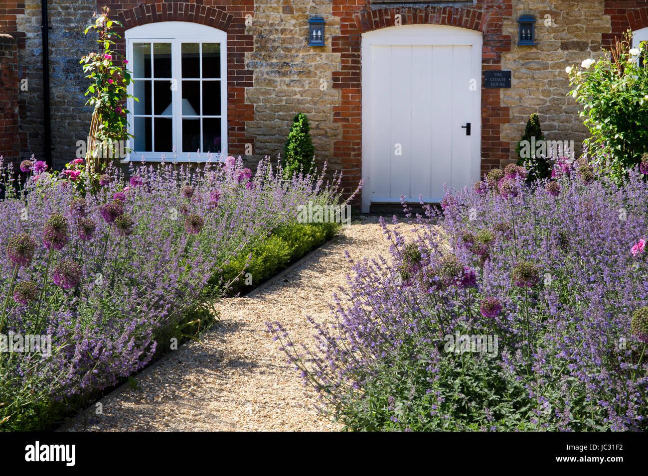 kiesweg mit boarder sommerpflanzen im englischen garten stockfoto